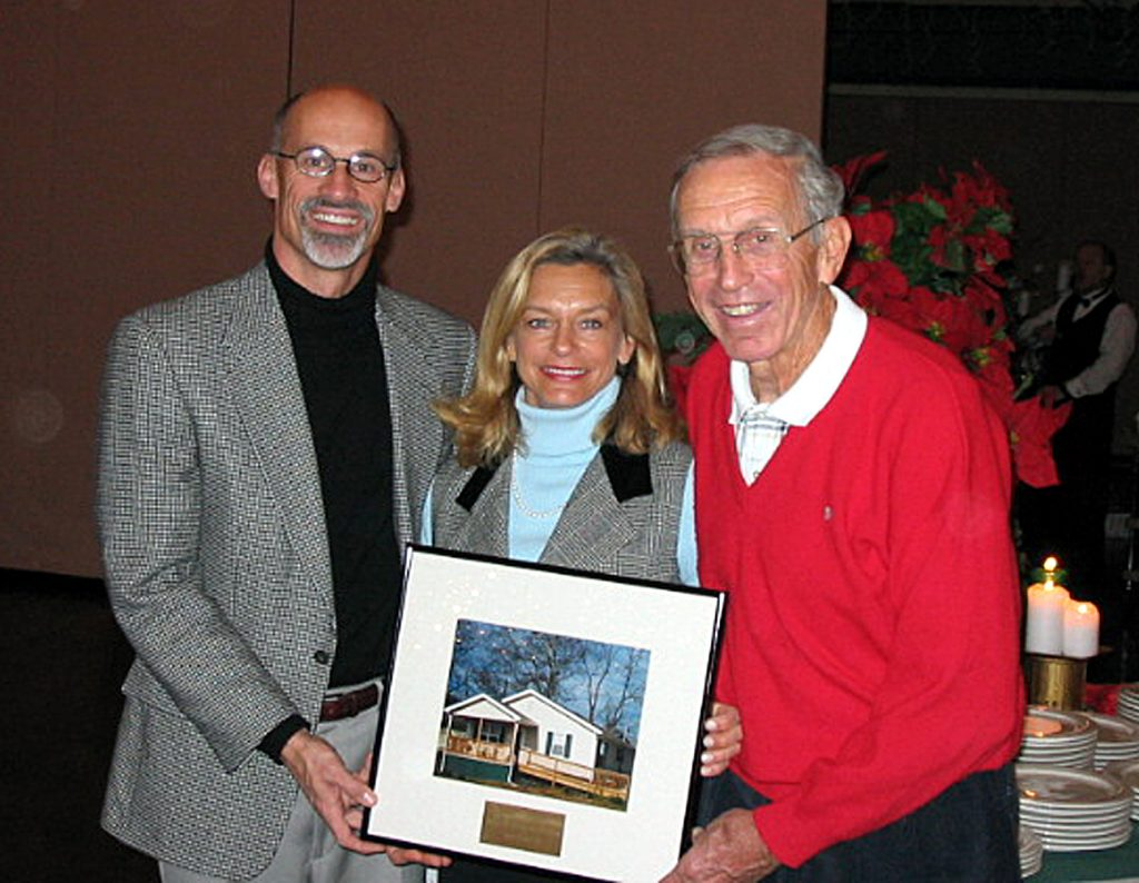 Bob Temple posing with a photo of a home that he helped build